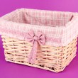 Wicket basket with pink fabric and bow, on color background — Stok fotoğraf