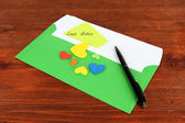 Note in envelope with pen on wooden background — Stock Photo