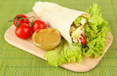 Kebab - grilled meat and vegetables, on wooden board, on bamboo mat background — Stok fotoğraf