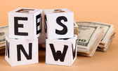 "White paper cubes labeled ""News"" with money on beige background — Zdjęcie stockowe"