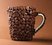 Cup of coffee beans, on brown background — Stock Photo