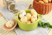 Tender young potatoes with sour cream and herbs in pan on wooden board on table close-up — Stok fotoğraf