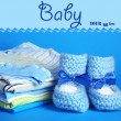 Pile of baby clothes on blue background - Zdjęcie stockowe