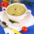 Nourishing soup in pink pon blue tablecloth close-up — Stock Photo #25903629