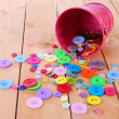 Stock Photo: Colorful buttons strewn from bucket on wooden background