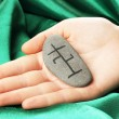 Fortune telling  with symbols on stone in hand on green fabric background - Stock Photo