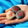 Fortune telling  with symbols on stone in hand on blue fabric background - Stock Photo