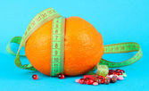 Orange with measuring tape and multicolor pills, on color background — Stock Photo
