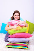 Beautiful young girl with pillows in room — Stok fotoğraf