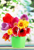 Beautiful tulips in bouquet on table on bright background — Stock Photo