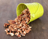 Overturned bucket with nuts on wooden background — Stock Photo