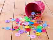 Colorful buttons strewn from bucket on wooden background — Stock Photo