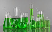 Test-tubes with green liquid on gray background — Stock Photo