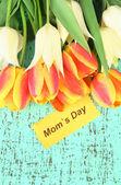 Belles tulipes blanches et orange sur fond en bois de couleur — Photo