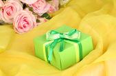 Beautiful gift on flowers background — Stock Photo
