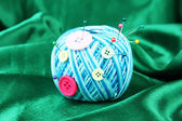 Colorful buttons and wool ball, on color fabric background — Stock Photo