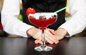 Barmen hand with shaker pouring cocktail into glass, on close up — Stockfoto