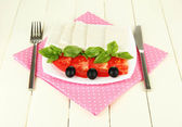 Sheep milk cheese, with basil and tomato on color napkin on wooden background — 图库照片