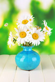 Beautiful bouquet chamomiles in vase on wooden table on natural background — Stock Photo