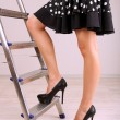 Woman climbing up ladder in office — Stock Photo #25992125