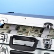 Suitcase with 100 dollar bills on blue background — Stock Photo