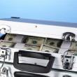 Suitcase with 100 dollar bills on blue background — Stock Photo #26013731