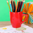 Colorful pencils in cup on table on green background — Foto Stock