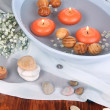 Beautiful candles swim in beautiful plate on wooden table close-up — Stock Photo