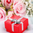 Roses and gift box on a white cloth — Stock Photo