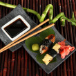 Tasty Maki sushi - Roll on plate on bamboo mat — Stock Photo #26015099