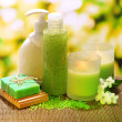 Stock Photo: Cosmetics bottles and natural handmade soap on green background