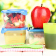 Tasty lunch in plastic containers, on wooden table on bright background — Stock Photo #26015219