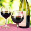 Two glasses of wine and bottle on table on nature background — Stock Photo