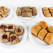Sweet baklava on plates isolated on white — Stock fotografie