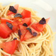Spaghetti with tomatoes and basil leaves close-up — Stock Photo
