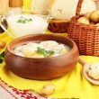 Tender young potatoes with sour cream and herbs in wooden bowl on tablecloth close-up - Stock Photo