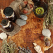 Composition with old papers, herbs, stones and bottles with symbols on wooden background — Stock Photo