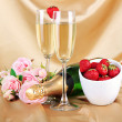 Romantic still life with champagne, strawberry and pink roses, on color fabric background — Stock Photo #26017187