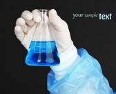 Glass tube with fluid in scientist hand during medical test on black background — Stock Photo