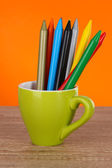 Colorful pencils in cup on table on orange background — Fotografia Stock