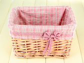 Wicket basket with pink fabric and bow, on color wooden background — Stock Photo