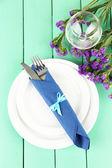 Tenedor y cuchillo envuelven en la servilleta, sobre la placa, en color madera — Foto de Stock
