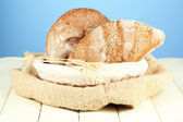 Bread in wicker basket, on wooden table, on color background — Stock Photo