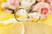 Wedding rings tied with ribbon on bright background — Stock Photo