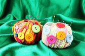 Bunte knöpfe und multicolor wolle bälle, auf farbigem stoff hintergrund — Stockfoto