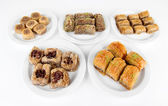 Sweet baklava on plates isolated on white — Stock Photo