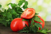 świeże pomidory i młodych roślin na drewnianym stole na naturalne tło — Zdjęcie stockowe