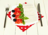 Sheep milk cheese, with basil and tomato on color napkin on wooden background — Stock Photo