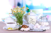 Table setting with chamomiles on wooden table on window background — Stock Photo