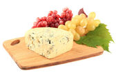 Tasty blue cheese and grape on cutting board, isolated on white — Stock Photo